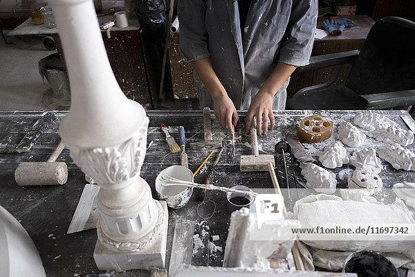 Hands of Caucasian sculptor holding tools