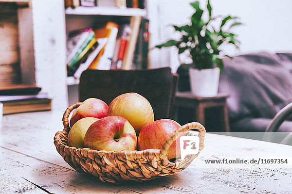 Basket of apples on wooden table in livingroom
