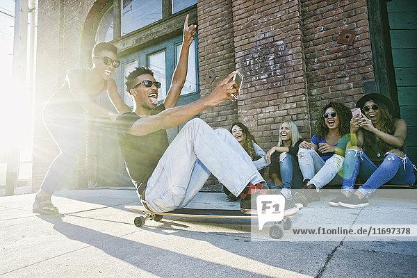 Woman pushing friend sitting on skateboard in city