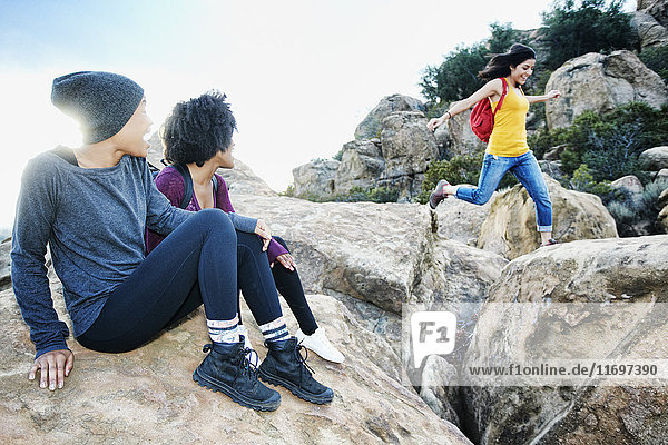 Women watching friend jumping on rock formation