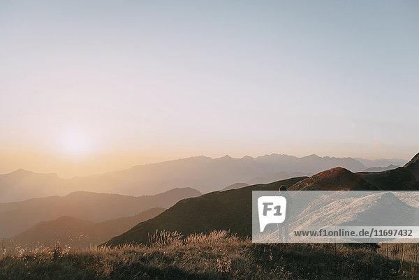 Caucasian man admiring scenic view of sunset on mountain