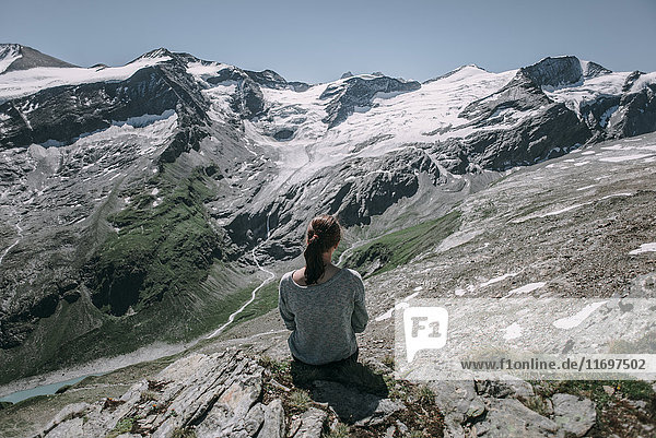 Caucasian woman sitting on rock admiring scenic view of mountain