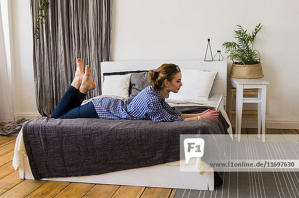Caucasian woman laying on bed reading digital tablet