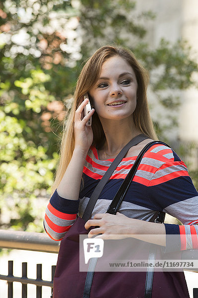 Smiling Caucasian woman carrying purse talking on cell phone