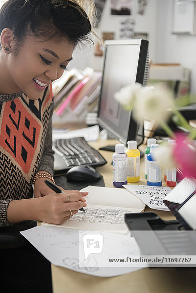 Mixed Race woman sitting near computer drawing design on paper