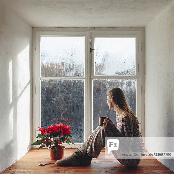 Caucasian woman sitting in window sill drinking coffee in pajamas