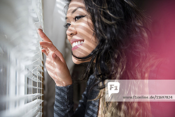 Mixed Race woman peeking out window behind blinds