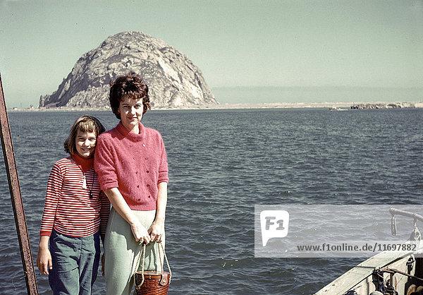 Caucasian mother and daughter posing near ocean