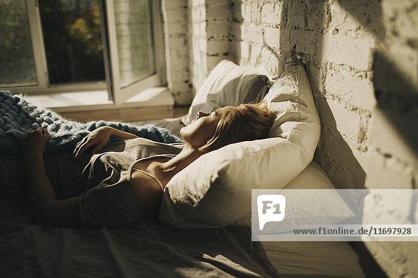 Caucasian woman sleeping in bed near open window
