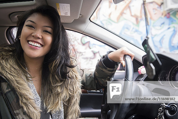 Portrait of smiling Mixed Race woman driving car