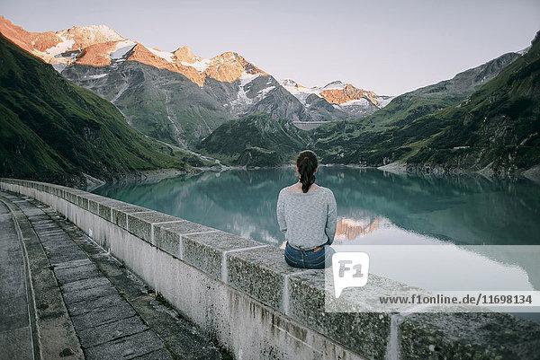 Caucasian woman sitting on wall at mountain lake