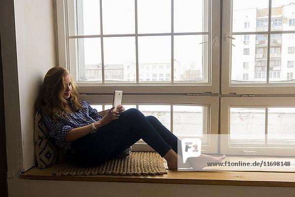Caucasian woman sitting on window sill reading digital tablet