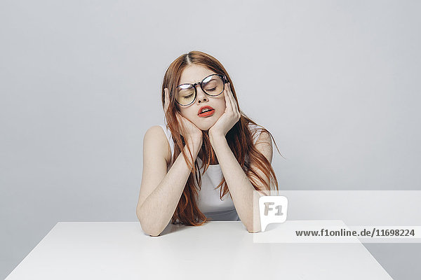 Frustrated Caucasian woman sitting at table