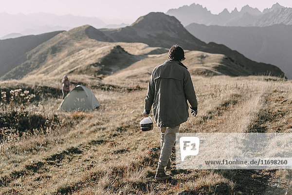 Caucasian man carrying bucket of snow to tent on mountain