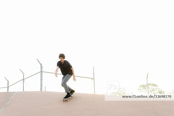 Hispanic man skateboarding in skate park