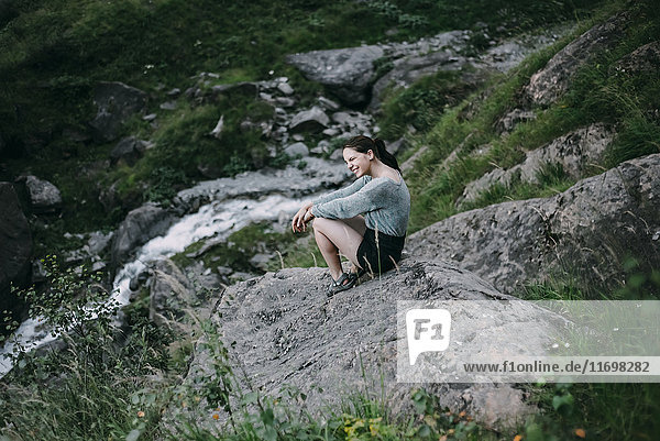 Smiling Caucasian woman sitting on rock on hill