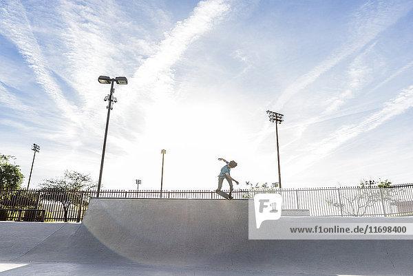 Hispanic man riding skateboard at skate park