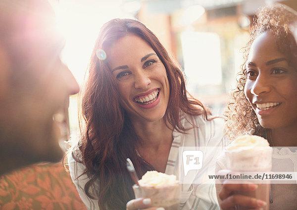 Portrait begeisterte junge Frau beim Milchshake trinken mit Freunden