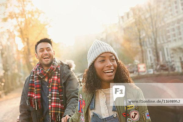 Lachendes junges Paar auf der urbanen Herbststraße  Amsterdam