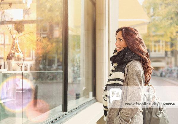 Lächelnde junge Frau beim Schaufensterbummel im Stadtgeschäft