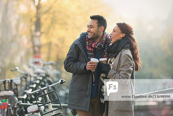 Lächelndes junges Paar in warmer Kleidung trinkt Kaffee in der Stadt