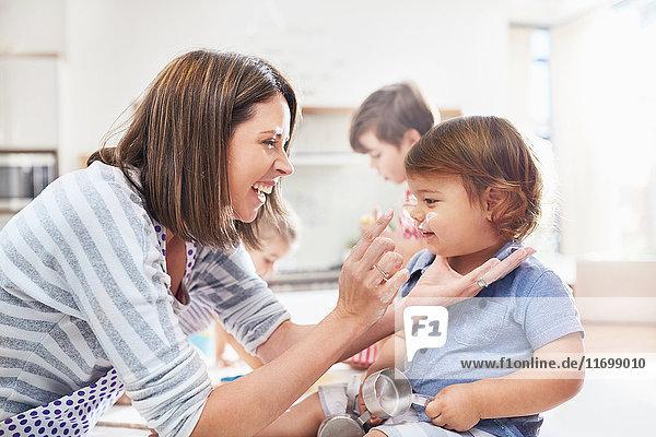 Verspielte Mutter und Sohn mit Mehl auf der Nase Backen in der Küche