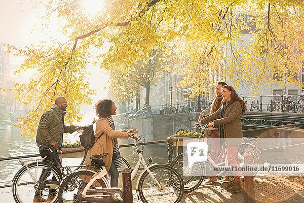 Freunde mit Fahrrädern am sonnigen Herbstkanal in Amsterdam