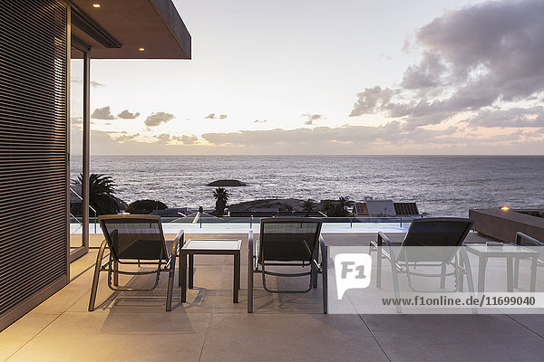 Lounge chairs on luxury patio with sunset ocean view