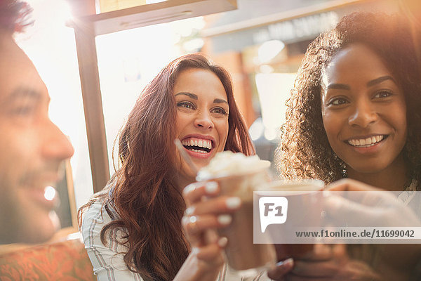 Enthusiastic friends toasting coffee cups at cafe