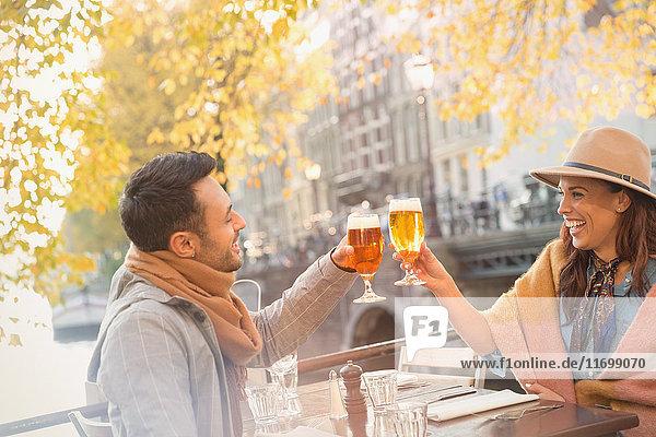 Junges Paar rösten Biergläser im städtischen Herbstcafé  Amsterdam