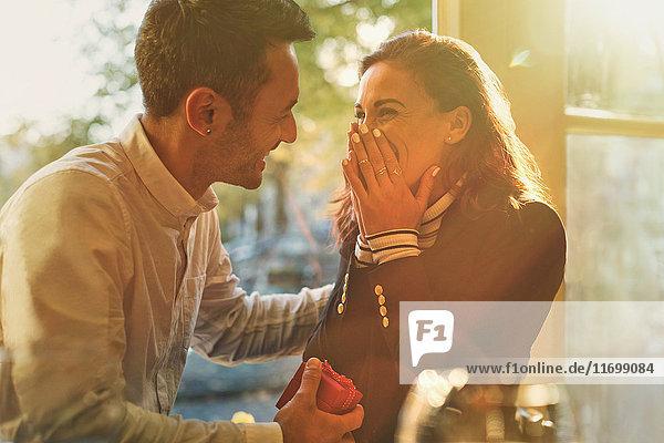 Freund schlägt überraschte  glückliche Freundin im Cafe vor