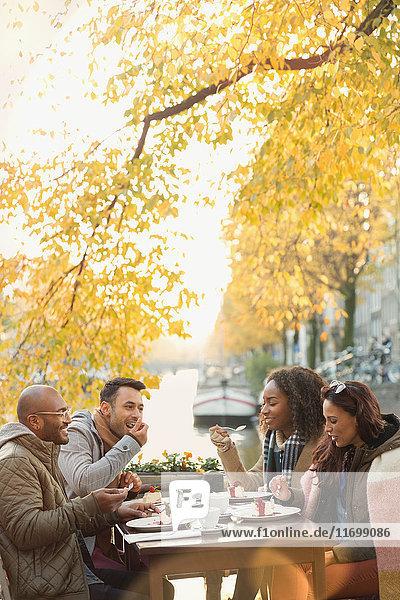 Freunde essen Dessert und trinken Kaffee im Herbst Bürgersteig Cafe entlang des Kanals