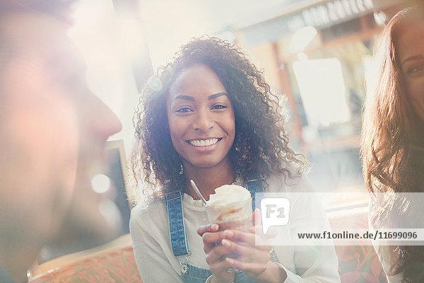 Portrait lächelnde junge Frau trinkt Milchshake mit Freunden im Cafe