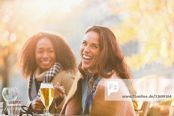 Portrait lachende junge Frauen Freunde beim Biertrinken im herbstlichen Straßencafé
