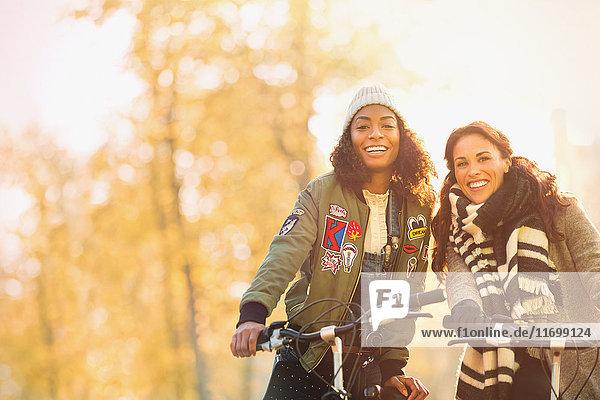 Portrait lächelnde junge Frauen Freunde Radfahren auf der Herbststraße