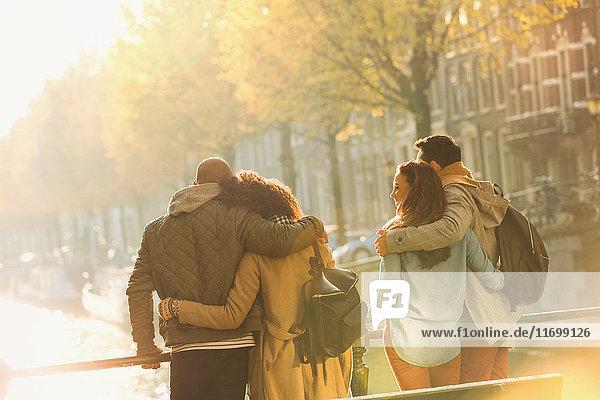 Junge Paare umarmen sich auf der Brücke über den sonnigen Herbstkanal  Amsterdam