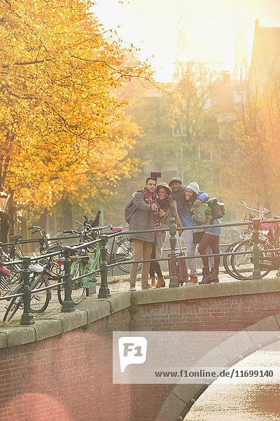 Freunde nehmen Selfie mit Selfie-Stick auf der Herbstbrücke über den Kanal in Amsterdam