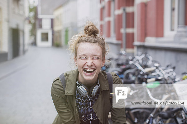 Portrait enthusiastic  laughing young woman with headphones on city street Portrait enthusiastic, laughing young woman with headphones on city street