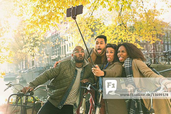 Verspielte junge Freunde mit Fahrrädern  die ein Gesicht mit Selfie-Stick am Herbstkanal machen  Amsterdam