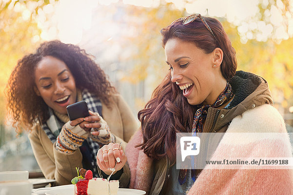 Junge Frau mit Fotohandy fotografiert Freund essen Käsekuchen Dessert auf dem Bürgersteig Cafe