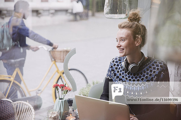 Smiling young woman with headphones using laptop in urban cafe window