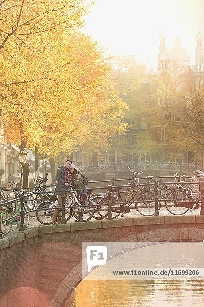 Portraitpaar mit Fahrrädern auf städtischer Herbstbrücke über den Kanal  Amsterdam