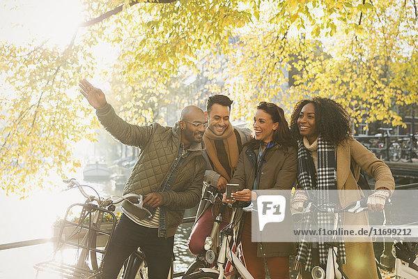 Freunde mit Fahrrädern am sonnigen Herbstkanal