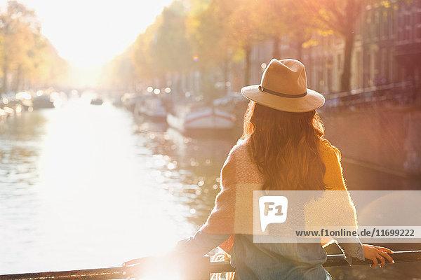 Frau mit Blick auf den sonnigen Herbstkanal  Amsterdam