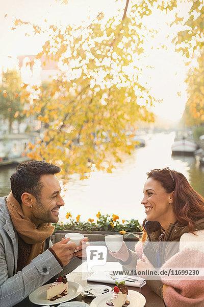 Junges Paar trinkt Kaffee und isst Käsekuchen-Dessert im herbstlichen Straßencafé entlang des Kanals.