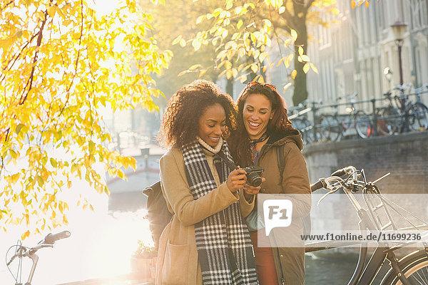 Lächelnde junge Frauen mit Digitalkamera am sonnigen städtischen Herbstkanal  Amsterdam