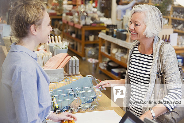 Smiling female shopper and cashier talking in shop