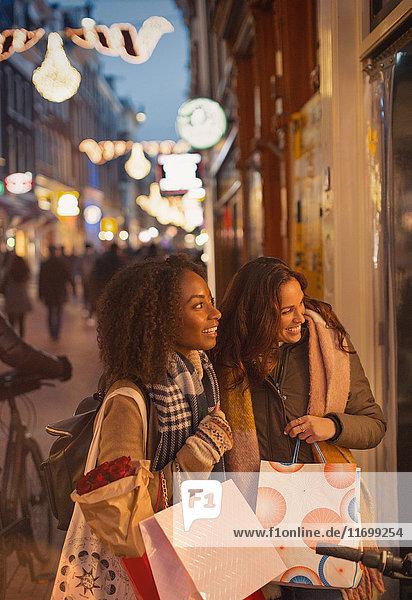 Junge Frauen beim Schaufensterbummel an der urbanen Nachtstraße