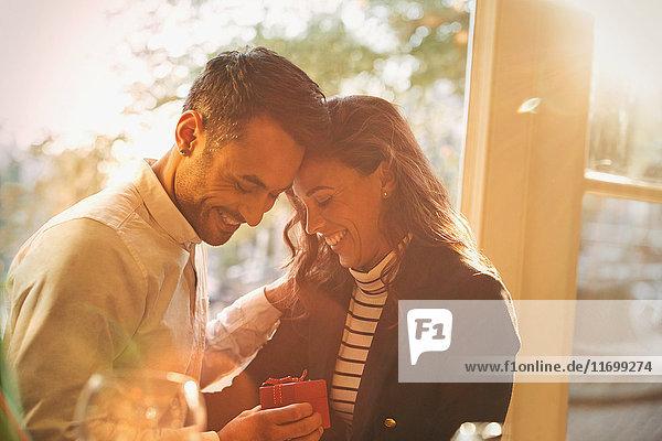 Zärtlicher  romantischer Freund schenkt Freundin im sonnigen Cafe