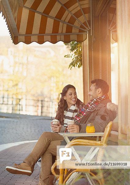 Junges Paar trinkt Milchshakes im Straßencafé